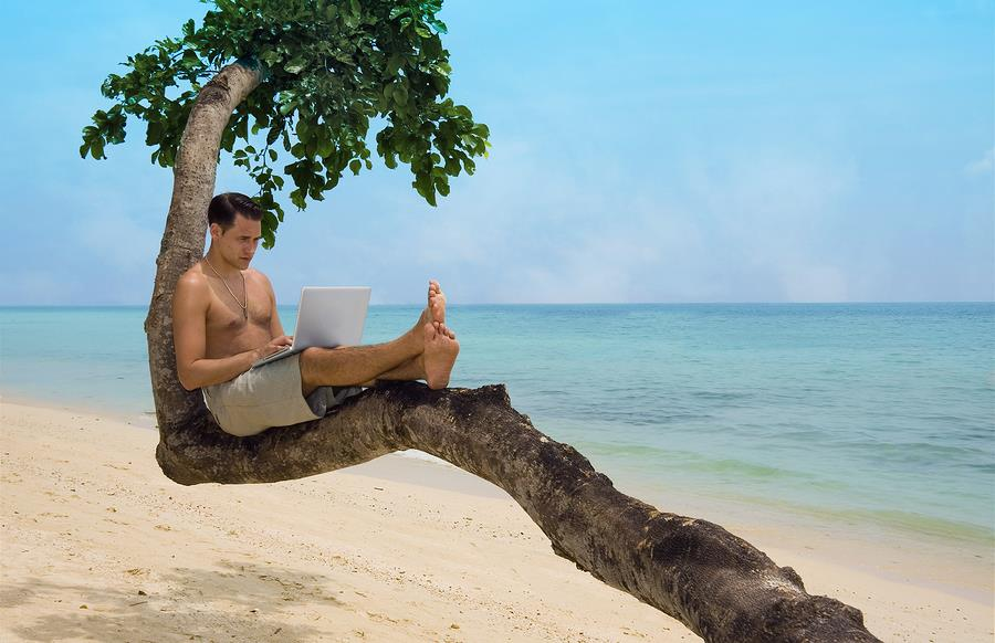 Attractive man with laptop seated in a tree on a tropical beach.